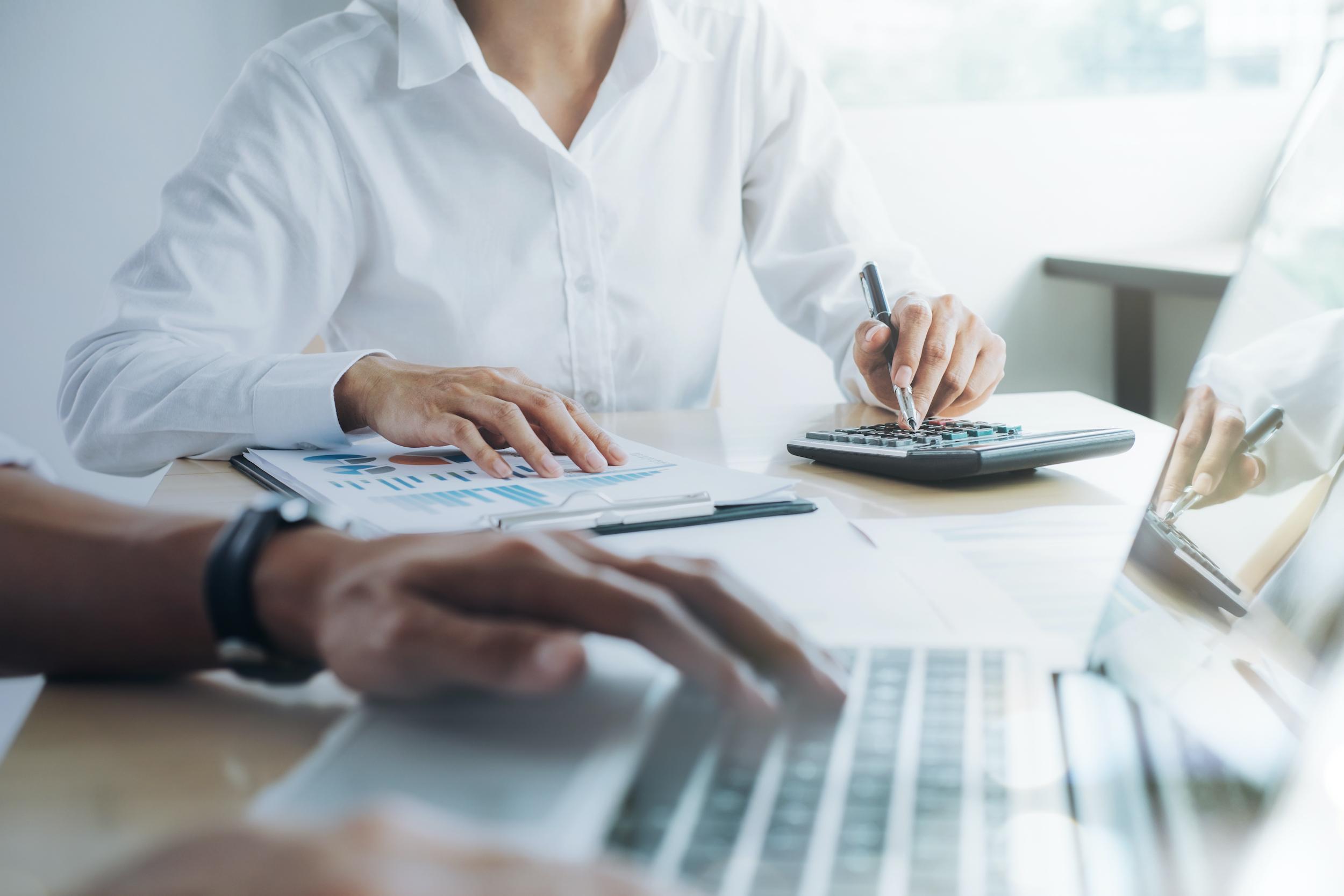 Mains d'hommes travaillant sur un bureau avec un ordinateur et une calculette